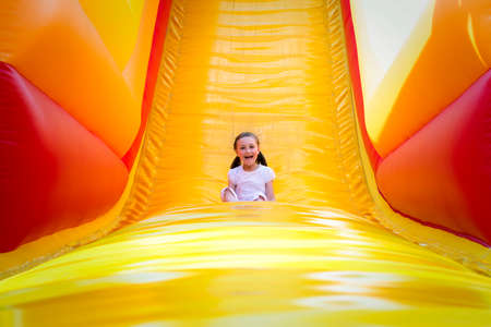 bounce: Happy little girl having lots of fun on a jumping castle while sliding.