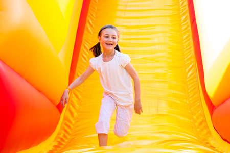 niña feliz que tiene un montón de diversión en un castillo inflable mientras se desliza.
