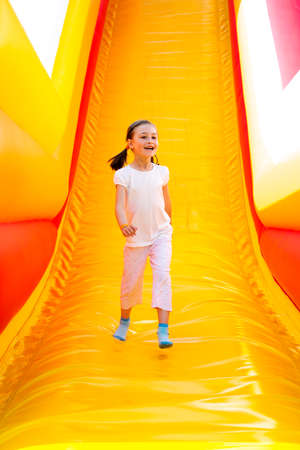 blowup: Happy little girl having lots of fun on a jumping castle while sliding.