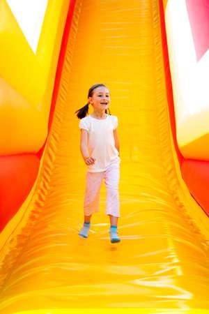 brincolin: niña feliz que tiene un montón de diversión en un castillo inflable mientras se desliza.