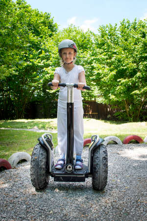 Young girl ride on segway in park. Stock Photo