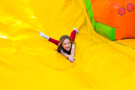 Happy little girl having lots of fun on a jumping castle while sliding. Фото со стока - 81816323