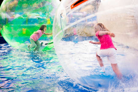 Two young girls playing inside a floating water walking ball.