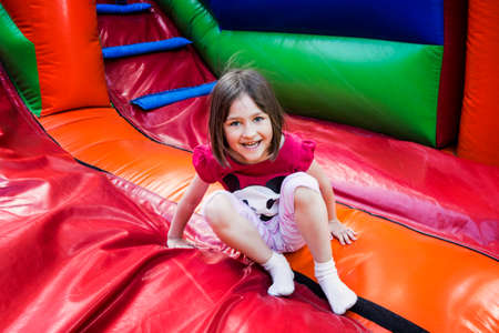 Happy little girl having lots of fun on a jumping castle while sliding. Zdjęcie Seryjne - 93554334
