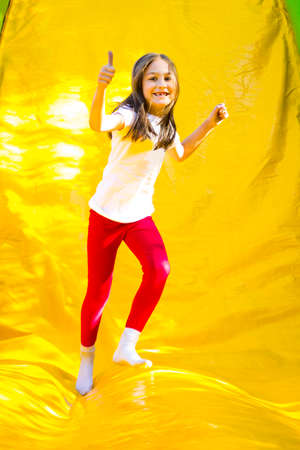 Happy little girl showing thumb up after sliding on a inflatable castle.