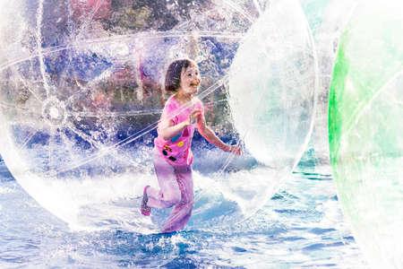Young girl playing inside a floating water walking ball. Banco de Imagens