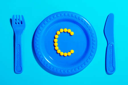 Letter C created from yellow pills on children's plate with cutlery toy. Medical concept for eating vitamin C.