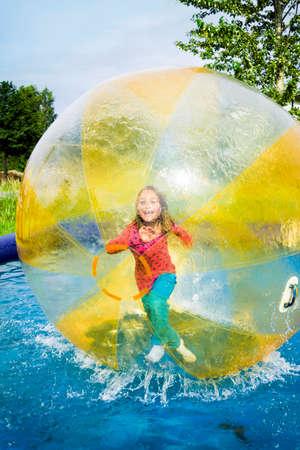 Young girl running inside a floating water walking ball. Banco de Imagens