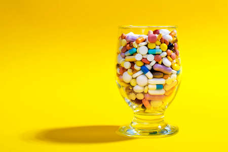 Glass full of colorful pills on a yellow background. Creative composition.