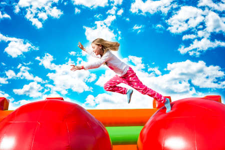 Happy little girl having lots of fun while jumping from ball to ball on an inflate castle. Stock fotó