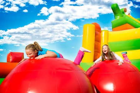 Glückliche kleine Mädchen, die viel Spaß beim Springen von Ball zu Ball auf einer aufgeblasenen Burg haben.