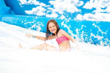 Young girl on water slide at aquapark. Summer holiday.