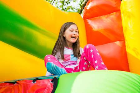 Bambina felice che si diverte molto su un castello di salto durante lo scorrimento.