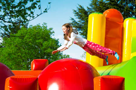 Happy little girl having lots of fun while jumping from ball to ball on an inflate castle. Stock Photo