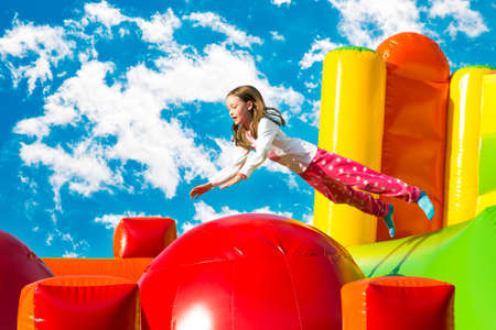Happy little girl having lots of fun while jumping from ball to ball on an inflate castle. 版權商用圖片