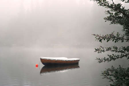 A row boat anchored on the calm lake in the foggy autumn. Reklamní fotografie