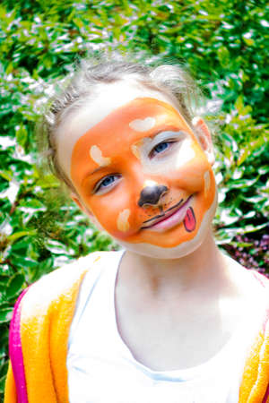 Young girl smiling with her face painted as a dog.