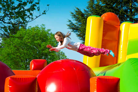 Happy little girl having lots of fun while jumping from ball to ball on an inflate castle. Imagens