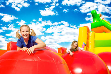 Happy little girls having lots of fun while jumping from ball to ball on an inflate house. Stock Photo
