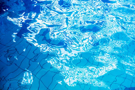 Blue swimming pool rippled water detail with sunny reflection.
