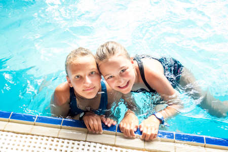 Portrait of two happy sisters in swimming pool during vacation.