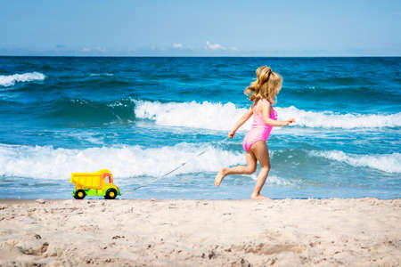 Little girl playing on the sandy beach, pulling a yellow lorry dump with sea in background.
