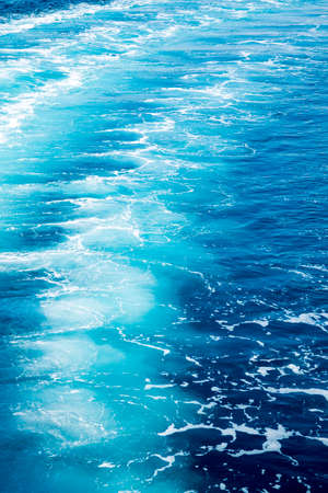 Trail on ocean water surface behind of fast moving powerful engines.