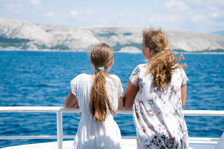 Two girls stand at deck of ship and look at the ocean and island, Croatia. Zdjęcie Seryjne