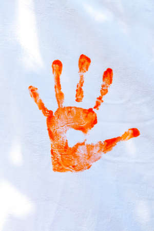 Orange hand paint done by kids on white fabric.