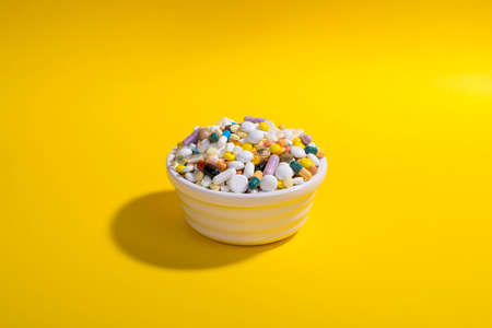 Bowl full of colorful pills on yellow background. Creative composition.