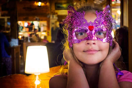 Beautiful Girl in a Carnival mask in the restaurant. Zdjęcie Seryjne