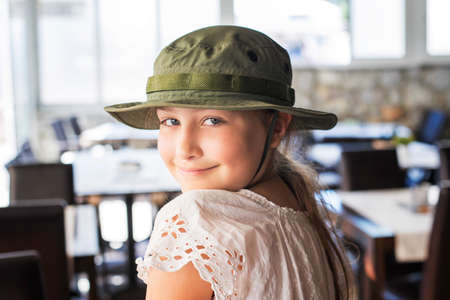 A beautiful little blond girl child in military hat enjoying the time in a restaurant, indoors. Zdjęcie Seryjne