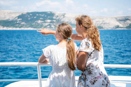 Young girl stands at deck of ship and points out across the horizon to her sister, enjoying a family cruise ship vacation together. Croatia.
