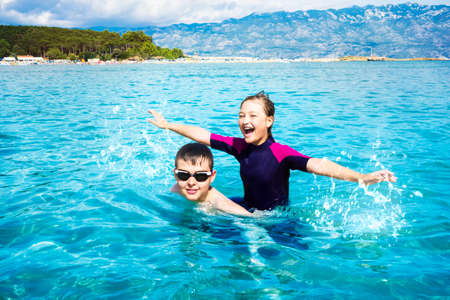 Boy and girl splashing in the water and playing in the ocean while on vacation. Croatia.
