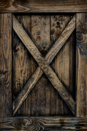 Detail of old wooden door with weathered planks, cross, knots and rings.