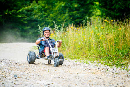 Man enjoying a fast ride go kart downhill in a mountain off road.