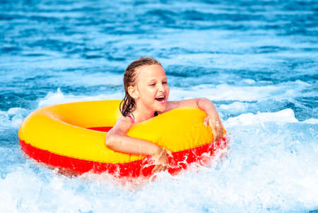 Young girl in swimming ring playing in the waves on a sunny day.  Baltic Sea.