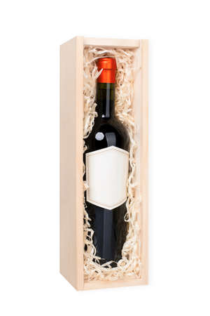 Open wooden box with vine bottle with blank label filled with shreded paperstraw. Isolated on white.