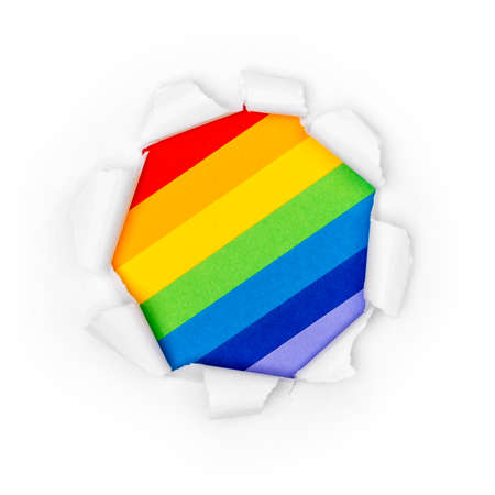 Paper hole in white paper with ragged edges with rainbow colors background. Stock fotó