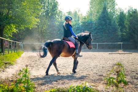 A young girl riding her pony during riding lesson, outside. Natural sun rays shining in dust during sunset. Stock fotó