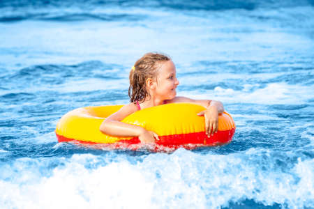 Happy young girl in swimming ring playing in the waves on a sunny day.  Baltic Sea.