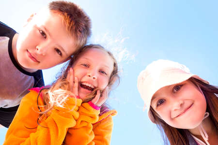 Group of three happy, surprised children looking down at the viewer.