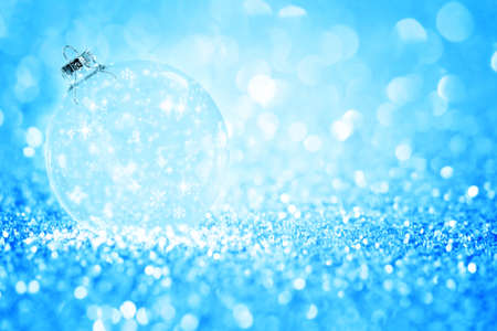 Transparent Christmas ball with snowflake against glitter bright blue background. Stock Photo