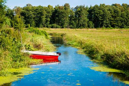 Summer landscape of polish cottage with boat on slow river.