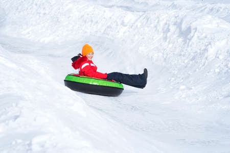 Child girl on snow tubes downhill at winter day. Stock fotó