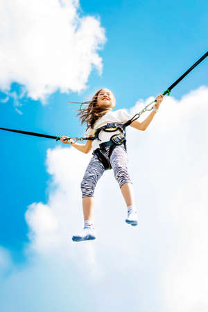 Little girl bouncing high in the air using a bungee trampoline.