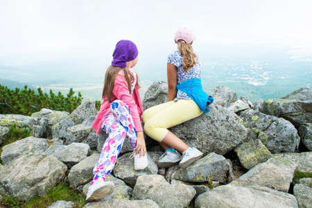 Two girls sitting and resting after hiking on mountain peak looking at green valley in Tatra mountain. Reklamní fotografie
