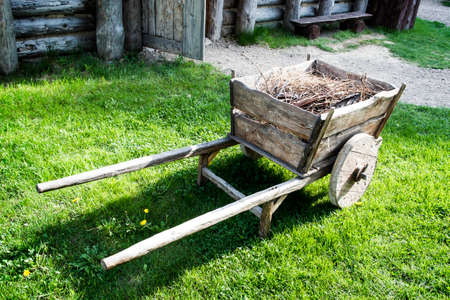 Vintage cart with brushwood in front of old wooden house.