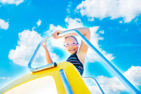 A happy young girl prepares to slide down a water slide.