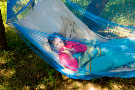 Child girl relaxing in a sunny hammock with mosquito net in forest. Reklamní fotografie